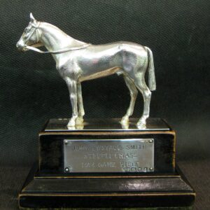 Silver horse on wooden stand.