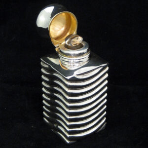 A rare unusually shaped silver perfume bottle.